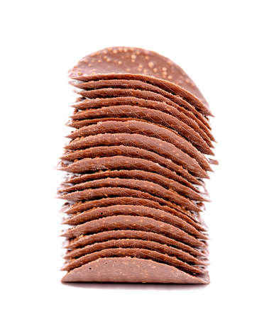 stack of dark chocolate chips is isolated on white background, close up