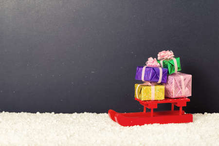 christmas spending: red festive sled with full gift boxes in snow on chalkboard background, winter holidays concept, copy space