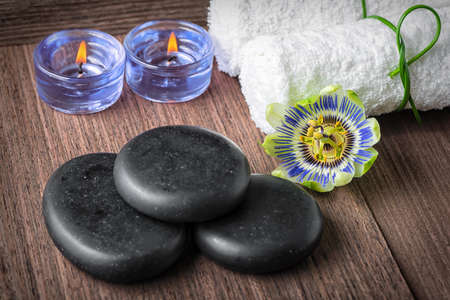 blue candles: spa composition of passiflora flower, blue candles, black zen stones and white towels on wooden background, close up