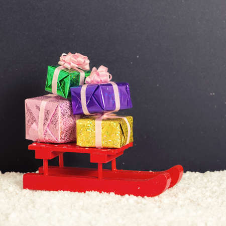christmas spending: red festive sled with full gift boxes in snow on chalkboard background, winter holidays concept, close up