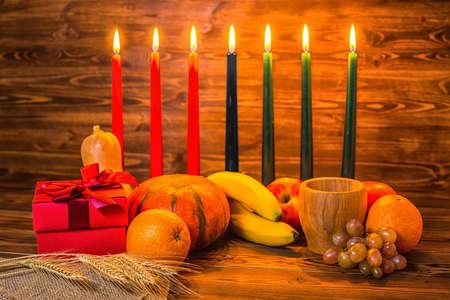 Kwanzaa vakantie concept met traditionele kaarsen, geschenkverpakking, pompoenen, oren van tarwe, druiven, sinaasappel, banaan, kom en vruchten op houten achtergrond
