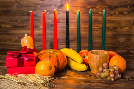 african Kwanzaa festive concept with decorative candles red, black and green, gift box, pumpkins, ears of wheat, grapes, orange, banana, bowl and fruits on wood background 免版税图像