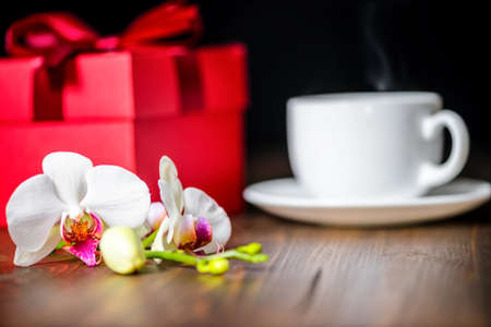 greeting red box with bow, orchid flower, phalaenopsis and cap of tea on wooden background, close up Stock Photo