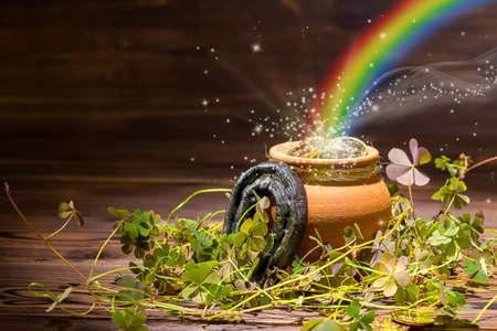 St. Patricks Tag Dekoration mit magischen Licht Regenbogen Topf voller Goldmünzen, Hufeisen und Kleeblätter auf Vintage-Holz-Hintergrund, Nahaufnahme Standard-Bild