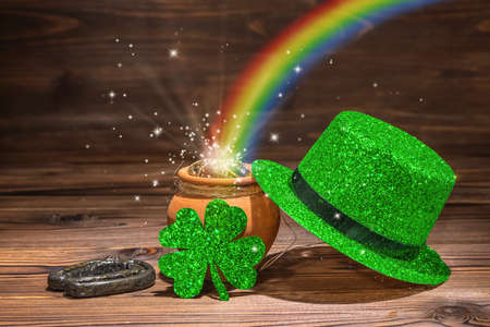 St Patricks day decoration with magic light rainbow pot full gold coins, horseshoe, green hat and shamrock on vintage wooden background, close up Stockfoto
