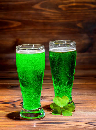 St Patricks day with glasses of green beer, leaf clover on vintage wooden background, close up