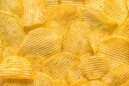 rippled natural potato chips with salt and greenery like background Stock Photo