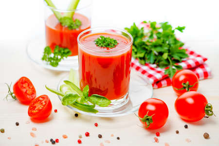 tomato juice in transparent glasses with parsley, basil,  cucumber and napkin on light wooden background, concept vegetarian food, close up Stock Photo