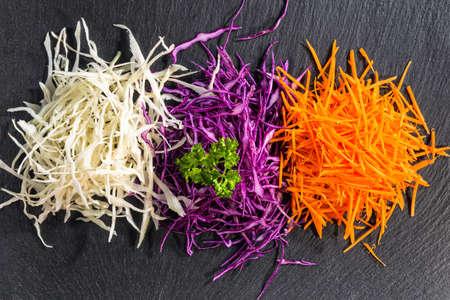 plat leggen van mix fijngehakte witte, rode kool, wortel versierd peterselie op zwarte leisteen achtergrond, concept gezond eten