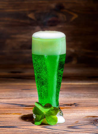 Glass of green spilled foam beer on vintage wooden background, St Patricks day with leaf clover, close up Stock Photo