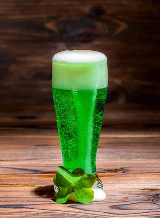 Het glas groen gemorst schuimbier op uitstekende houten achtergrond, St Patricks dag met bladklaver, sluit omhoog