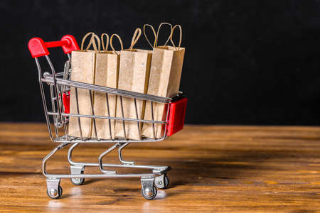 Concept of friday sale with shopping trolley, paper bags on wooden background over black, close up