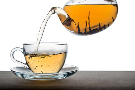 Close up of pouring tea from teapot on wooden over white background, mockup Stock Photo