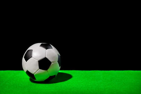 soccer ball on green grass over black background, concept of competitive sport