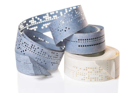 white and blue perforated punched tapes with old data  is isolated on background, close up