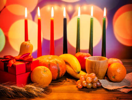 Kwanzaa festive concept with seven candles red, black and green, gift box, pumpkin, bowl and fruit on light blur bokeh background Stock Photo