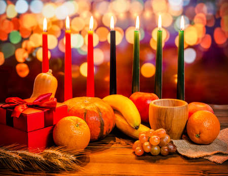 Kwanzaa holiday concept with decorate seven candles red, black and green, gift box, pumpkin, bowl and fruit on light blur bokeh background Stock Photo