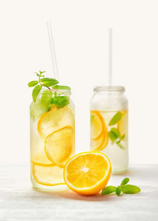 cold cut: homemade lemonade with fresh citrus and twig mint with drinking straw on wood background