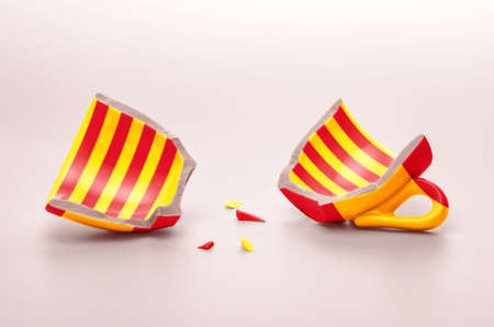 two halves of broken cup, patterned with flag of Spain and flag of Catalonia, independence concept