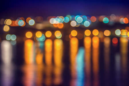 abstract blue circular bokeh background, city lights with reflection in water