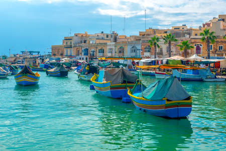 beautiful view of european harbor with village Marsaxlokk, market and traditional colorful Luzzu fishing boats, Malta