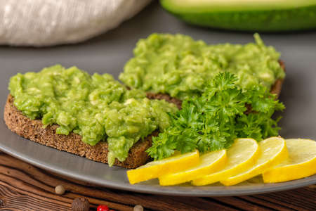 sandwiches with avocado green paste of mashed and cutted rye bread decorated alligator pear fruit, sliced lemon on plate on wooden background, vegetarian food Stock Photo