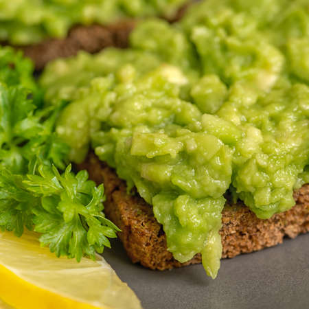 close up of  sandwiches with mexican sauce guacamole from avocado and toast decorated black bread, sliced lemon, parsley on plate, raw food Stock Photo