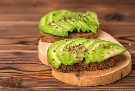 avocado sandwiches with cutted rye bread and sprinkle with pepper on wooden background, healthy eating