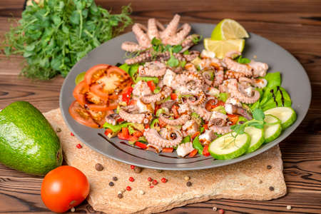salad with tentacles of octopus, lime, avocado and lettuce, decorated lime, avocado, tomato, sprigs of pea leaves and dry peppers, natural seafood Stock Photo
