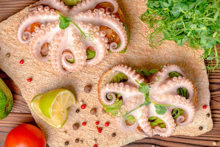 top view of sandwiches with octopus and bread toast decorated lime, avocado, tomato, sprigs of pea leaves and dry peppers Stock Photo