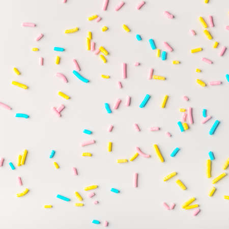colorful sprinkles on white background, flat lay