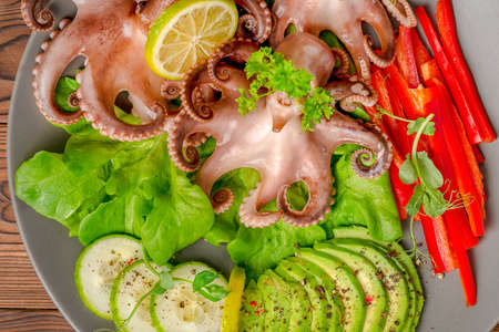 top down of octopus served with sliced avocado, lettuce, red pepper, lime, cucumber and sprig of pea leaves on plate, restaurant food