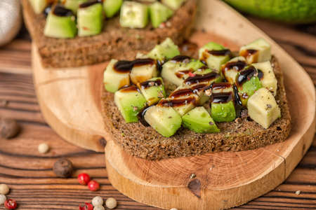 close up of chopped avocado on rye bread toast decorated drizzled with sauce and peppered on wooden background, healthy eating Stock Photo