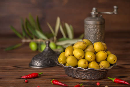 salted green olives in plate lie on wooden background decorated chilli pepers, Turkish style