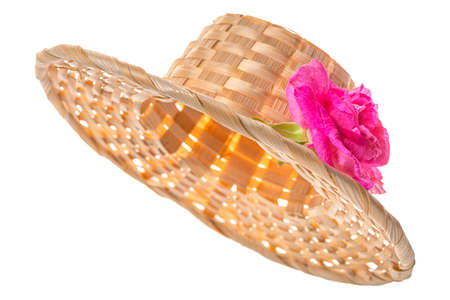 Straw hat with pink flower isolated on white background, close up