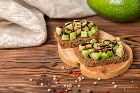 sandwiches with diced avocado, cutted rye bread decorated alligator pear fruit, drizzled with sauce and peppered on wooden background, raw food concept
