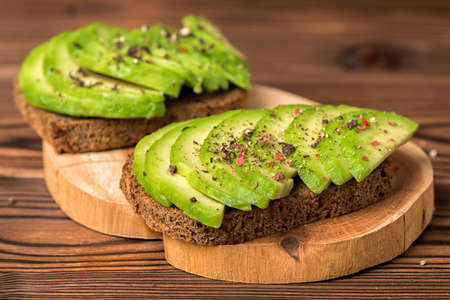 avocado sandwiches with rye bread toast and peppered on wooden background, healthy organic food concept