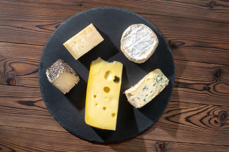 top view of portions cheese on wooden table, Italian, French food, concept of dairy products