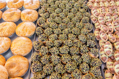 setting desserts of cookie with nuts at market, bakery storefront in Malta