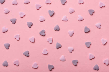 Beautiful sweet pink sprinkles of heart shapes over pink background, concept of St. Valentines Day Stock Photo