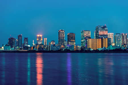 Beautiful seascape of Osaka city with modern buildings, lights and reflection in river, Japan, sunset