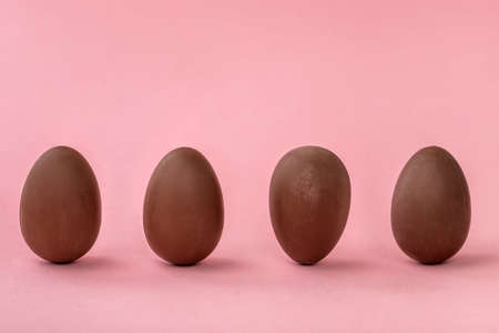 row of unstable chocolate eggs on pink background with copy space, funny creative concept 版權商用圖片