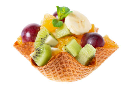 mix of fresh cuted fruits in waffle cone bowl is isolated on white background, concept of healthy dessert for children