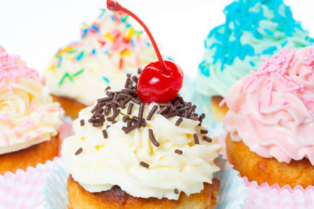 set of cupcakes with whipped cream decorated sprinkles and maraschino cherry