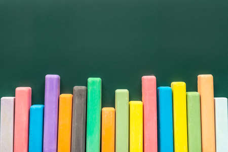 colored chalks on green blackboard, concept of advert in education or business