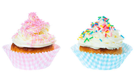 two cupcakes with whipped cream decorated sprinkles isolated on white background