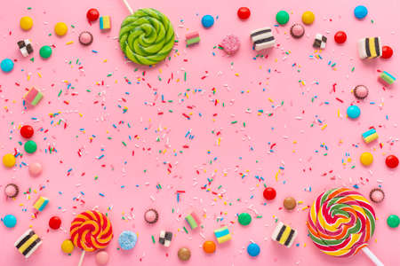 festive wreath background with assortment of colourful caramel candies, lollipops and sprinkles over pink Фото со стока