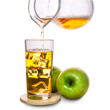 Glass with ice and pouring apple juice decorated fruits on stone isolated over white