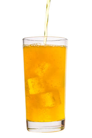Pouring fresh drink yellow soda with ice cubes in glass isolated on white
