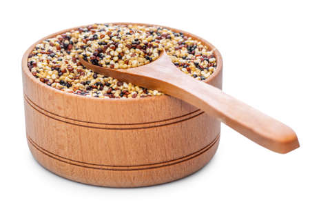 Dry quinoa seeds in natural wooden pot with spoon isolated on white